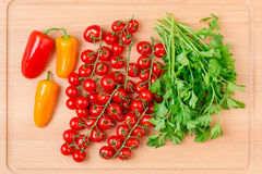 Tomatoes, mini bell peppers and parsley on wooden cutting board. Royalty Free Stock Photo