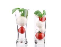 Tomatoes and mozzarella balls in glass. Stock Photos