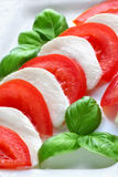 Tomatoes and mozzarella. Close up of sliced mozzarella cheese and fresh red tomatoes Stock Photo