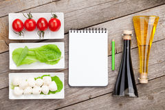 Tomatoes, mozzarella and green salad leaves with notepad for cop Royalty Free Stock Photos