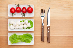 Tomatoes, mozzarella, green salad leaves and silverware Royalty Free Stock Photo