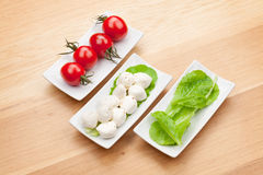 Tomatoes, mozzarella and green salad leaves Royalty Free Stock Photo