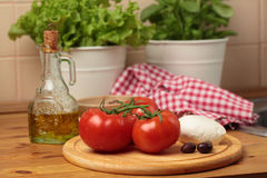 Tomatoes and mozzarella on a kitchen table Royalty Free Stock Photography