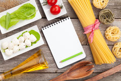 Tomatoes, mozzarella, pasta and green salad leaves with notepad Royalty Free Stock Photography