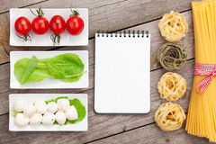 Tomatoes, mozzarella, pasta and green salad leaves with notepad Stock Photos