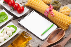Tomatoes, mozzarella, pasta and green salad leaves with notepad Royalty Free Stock Photos