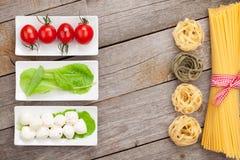 Tomatoes, mozzarella, pasta and green salad leaves Royalty Free Stock Image