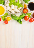 Tomatoes mozzarella salad making , ingredients on white wooden background, top view Royalty Free Stock Photography