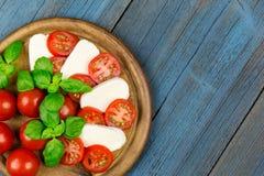 Tomatoes mozzarella slice basil Stock Images