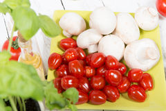 Tomatoes and mushrooms. Cherry tomatoes and some Paris mushrooms Royalty Free Stock Image