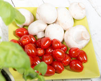 Tomatoes and mushrooms. Cherry tomatoes and some Paris mushrooms Royalty Free Stock Photography
