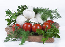 Tomatoes, mushrooms and herbs. On a kitchen board Royalty Free Stock Photos