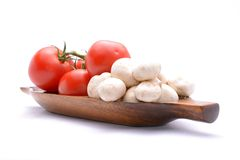 Tomatoes and mushrooms on wooden tray Royalty Free Stock Photography