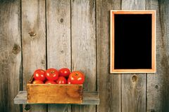 Tomatoes in an old box on a wooden shelf. Royalty Free Stock Photos