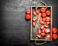 Tomatoes with old hatchet on the tray. On black chalkboard Royalty Free Stock Photo