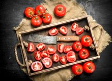 Tomatoes with old hatchet on the tray. On black chalkboard Royalty Free Stock Images