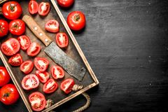 Tomatoes with old hatchet on the tray. On black chalkboard Stock Image