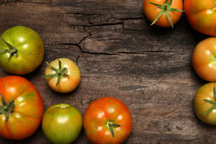 Tomatoes on old wooden background Stock Images