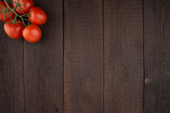 Tomatoes on old wooden table. Stock Images