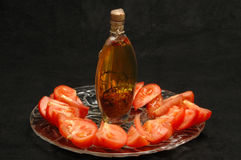 Tomatoes and olive oil. Tomato platter with  olive oil in a beautiful bottle Royalty Free Stock Photos