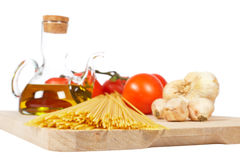 Tomatoes, olive oil, garlic and spaghetti Royalty Free Stock Photos
