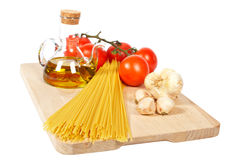 Tomatoes, olive oil, garlic and spaghetti Stock Images