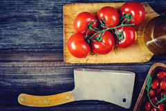 Tomatoes, olive oil, salad and cleaver on wooden background. Tomatoes on vine, cherry tomatoes, arugula, olive oil and old butcher cleaver on wooden table royalty free stock photo