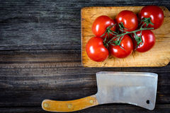 Tomatoes, olive oil, salad and cleaver on wooden background. Tomatoes on vine, cherry tomatoes, arugula, olive oil and old butcher cleaver on wooden table royalty free stock image
