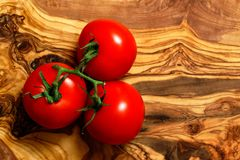 Tomatoes on an olive wood board Royalty Free Stock Photos