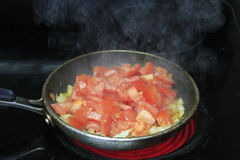 Tomatoes and onion cooking Royalty Free Stock Image