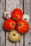 Tomatoes, onion and garlic on the table. Tomatoes, onion and garlic on the vintage wooden table royalty free stock image