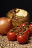 Tomatoes, onion and swede. Tomato, onion and tomato on a black background Stock Photos