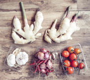 Tomatoes, onions, ginger and garlic on the old wood table. Stock Images