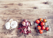 Tomatoes, onions, pepper and garlic on the old wood table. Stock Images