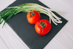 Tomatoes and onions. On a stone board Royalty Free Stock Photos