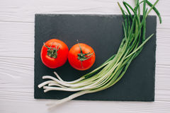 Tomatoes and onions. On a stone board Stock Photography
