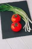 Tomatoes and onions. On a stone board Stock Images