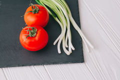 Tomatoes and onions. On a stone board Royalty Free Stock Photo