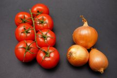 Tomatoes and onions. Vine-ripened tomatoes and some onions on an elegant black background with copy space to the right. Dust and optical imperfections have been stock photography