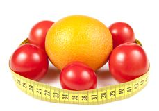 Tomatoes and orange with measuring band. Healthy diet conception Stock Photos