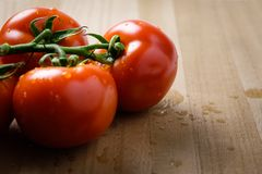 Tomatoes panicles on a wooden chopping board royalty free stock photo