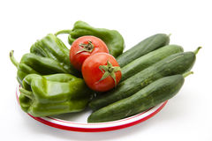 Tomatoes and paprika with cucumbers on plate Royalty Free Stock Photography