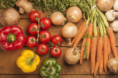 Tomatoes, paprikas, carrots, onions and champignons on wood Royalty Free Stock Photography