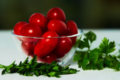 Tomatoes and parsley in a cup on the table. Tomatoes in a glass cup and parsley on a white table against the background of the street Stock Images