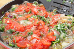 Tomatoes parsley and onion frying Royalty Free Stock Photo