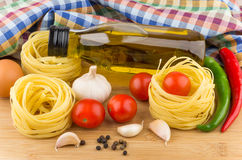 Tomatoes, pasta nests, bottle oil, chili peppers and garlic Stock Photography