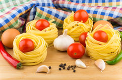 Tomatoes in pasta nests, chicken eggs, chili peppers and garlic Royalty Free Stock Photos