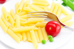 Tomatoes, peas, pasta and fork Stock Images