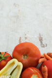 Tomatoes, pepper and carrots on wooden board Royalty Free Stock Images