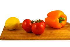 Tomatoes, pepper and lemon on wooden board isolated on white background royalty free stock images